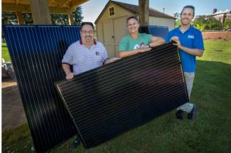 three people with solar panel