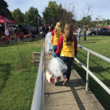 Students Walking with Recycling Bags at Football Tailgates